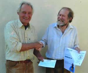Barry Evetts receiving a cheque from Jeremy Bell